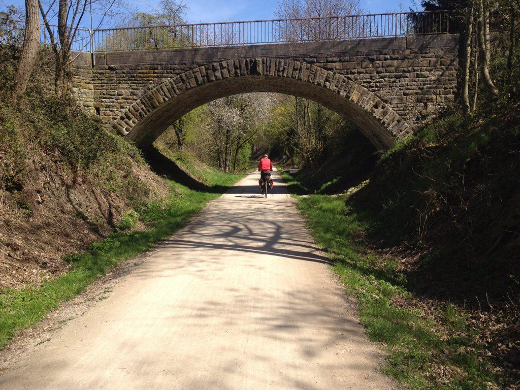 Radfahrer unterquert ein altes Viadukt auf einem mit Sand bedecken Weg.