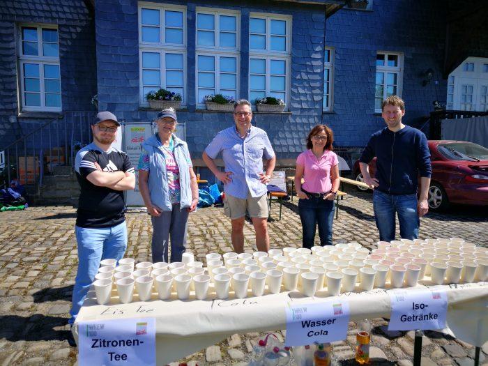 Männer und Frauen stehen vor einem Tisch mit Bechern, in denen verschiedene Getränke eingefüllt sind