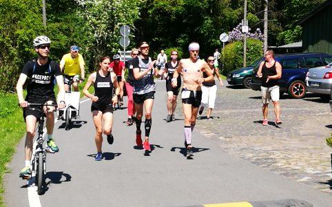Mehrere Männer und Frauen laufen in sportlicher Bekleidung über eine asphaltierte Straße