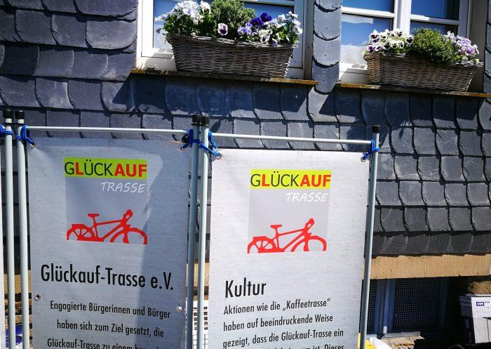 """Zwei Banner mit Beschriftung """"Glückauf-Trasse"""" gehen vor einem mit Schiefer belegten Haus."""