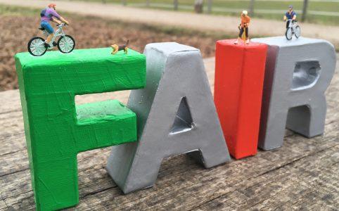 Auf bunten Buchstaben des Wortes Fair stehen Miniaturfiguren