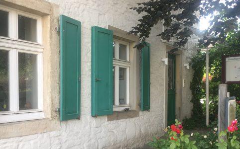 Altes Gebäude mit grünen Schlagläden an den Fenstern