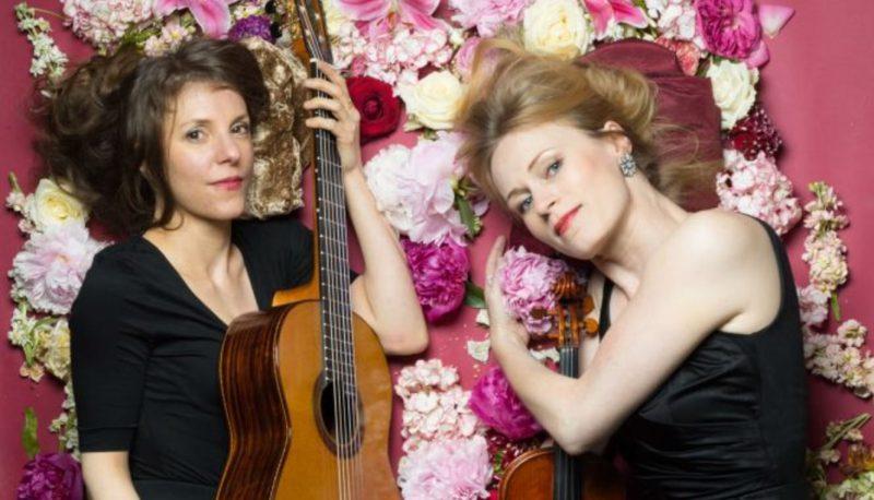 Zwei Frauen mit Gitarre und Geige liegen zwischen Blütenblättern